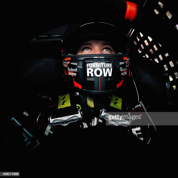 Martin Truex Jr driver of the Furniture Row/Denver Mattress Chevrolet sits in his car in the garage area during practice for the NASCAR Sprint Cup...