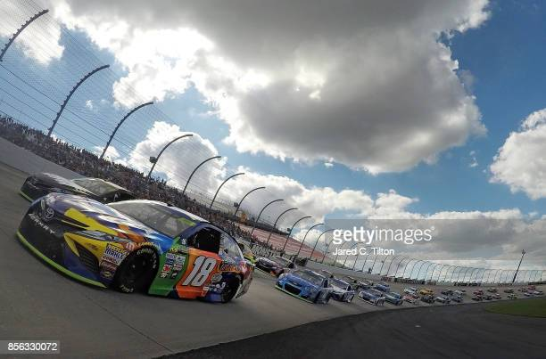 Martin Truex Jr driver of the Furniture Row/Denver Mattress Toyota and Kyle Busch driver of the MM's Caramel Toyota lead the field prior to taking...