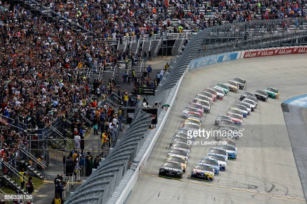 Martin Truex Jr driver of the Furniture Row/Denver Mattress Toyota and Kyle Busch driver of the MM's Caramel Toyota take the green flag to start the...