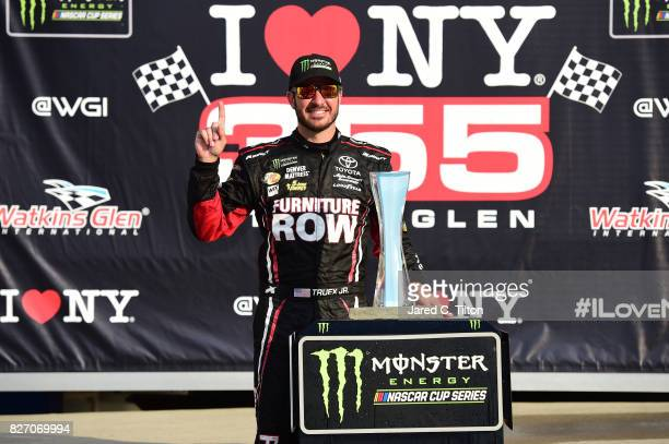 Martin Truex Jr driver of the Furniture Row/Denver Mattress Toyota celebrates in victory lane after winning the Monster Energy NASCAR Cup Series I...