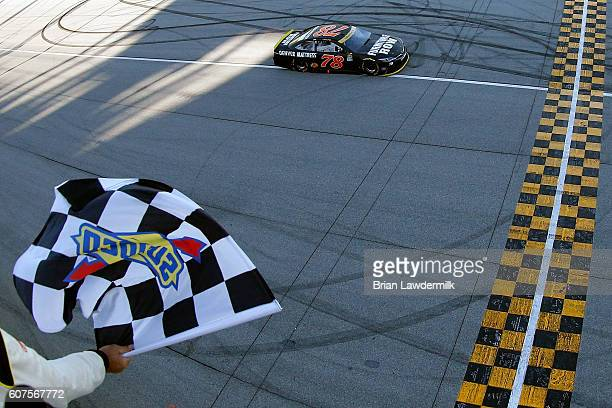 Martin Truex Jr driver of the Furniture Row/Denver Mattress Toyota approaches the finish line on his way to winning the NASCAR Sprint Cup Series...
