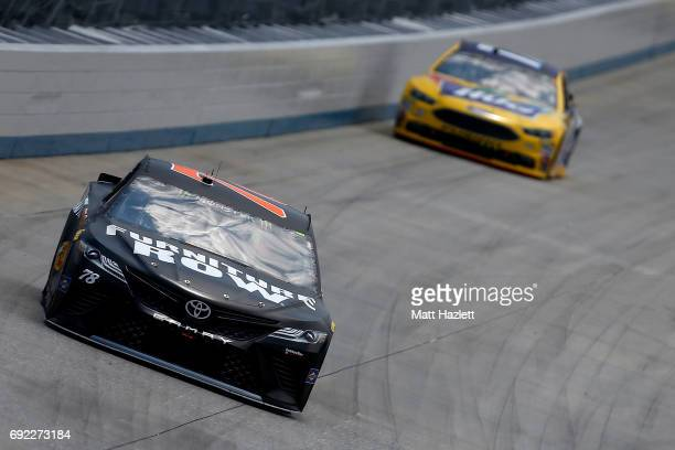 Martin Truex Jr driver of the Furniture Row/Denver Mattress Toyota leads Ricky Stenhouse Jr driver of the Little Hugs Ford during the Monster Energy...