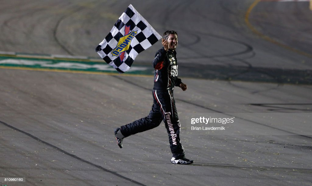 Martin Truex Jr., driver of the #78 Furniture Row/Denver Mattress Toyota, celebrates with the checkered flag after winning the Monster Energy NASCAR Cup Series Quaker State 400 presented by Advance Auto Parts at Kentucky Speedway on July 8, 2017 in Sparta, Kentucky.