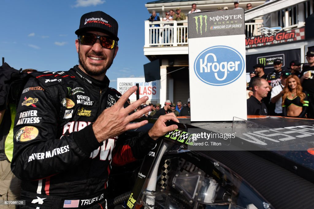 Martin Truex Jr., driver of the #78 Furniture Row/Denver Mattress Toyota, celebrates his fourth win by adding the winner's sticker to his car in Victory Lane after winning the Monster Energy NASCAR Cup Series I Love NY 355 at The Glen at Watkins Glen International on August 6, 2017 in Watkins Glen, New York.