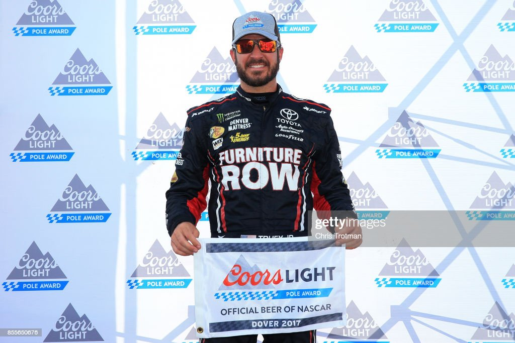 Martin Truex Jr., driver of the #78 Furniture Row/Denver Mattress Toyota, poses with the Coors Light Pole Award after qualifying in the pole position for the Monster Energy NASCAR Cup Series Apache Warrior 400 presented by Lucas Oil at Dover International Speedway on September 29, 2017 in Dover, Delaware.