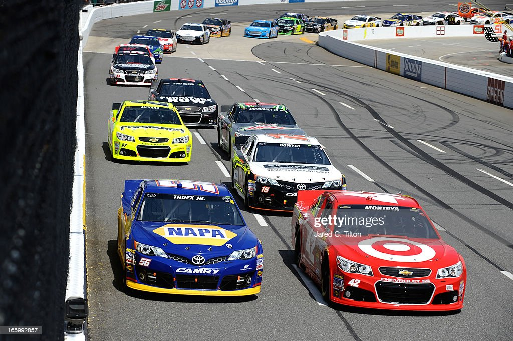 Martin Truex Jr., driver of the #56 NAPA Auto Parts Toyota, and Juan Pablo Montoya, driver of the #42 Target Chevrolet, lead a pack of cars down the frontstretch during the NASCAR Sprint Cup Series STP Gas Booster 500 on April 7, 2013 at Martinsville Speedway in Ridgeway, Virginia.