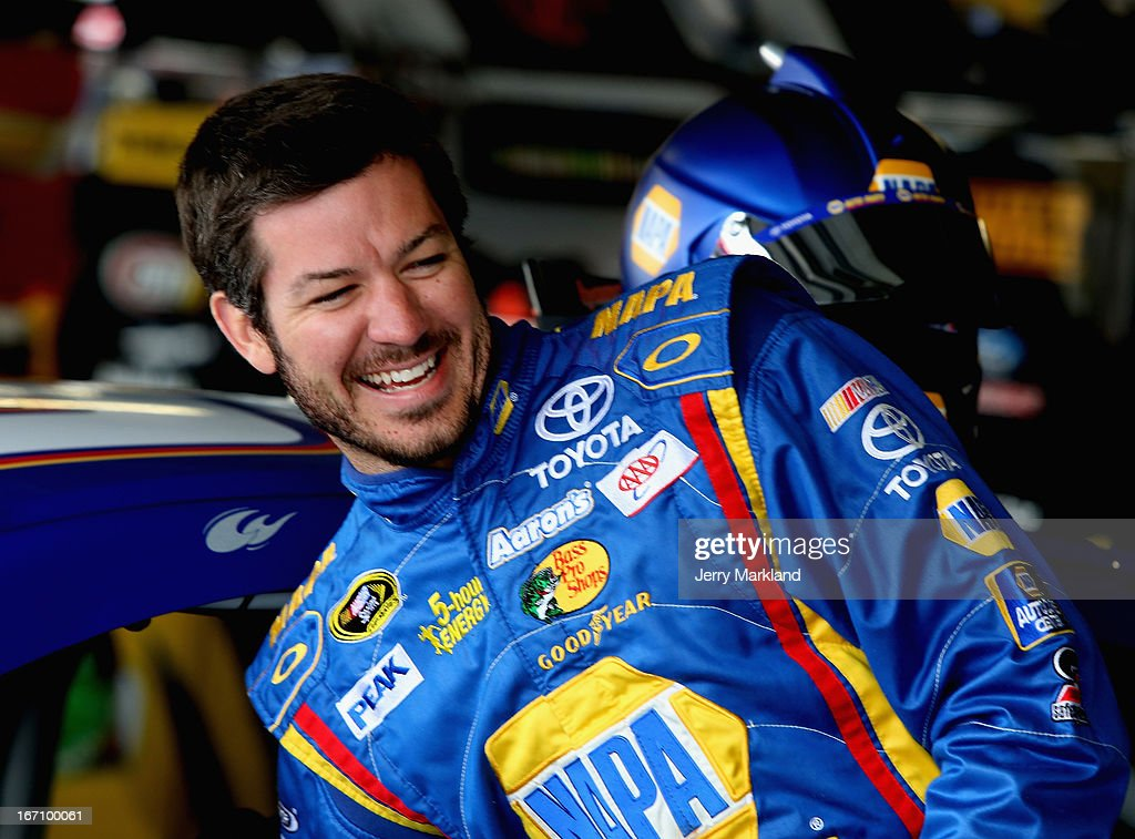 Martin Truex Jr., driver of the #56 NAPA Auto Parts Toyota, stands next to his car in the garage area during practice for the NASCAR Sprint Cup Series STP 400 at Kansas Speedway on April 20, 2013 in Kansas City, Kansas.