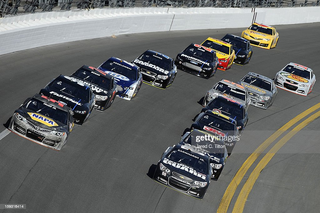 Martin Truex Jr., driver of the #56 Toyota, and Dale Earnhardt Jr., driver of the #88 Chevrolet, lead a group of cars through the tri-oval during NASCAR Sprint Cup Series Preseason Thunder testing at Daytona International Speedway on January 11, 2013 in Daytona Beach, Florida.