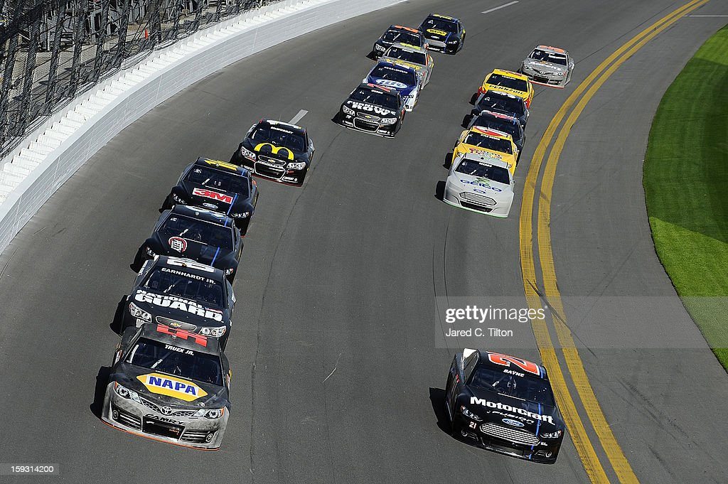 Martin Truex Jr., driver of the #56 Toyota, and Trevor Bayne, driver of the #21 Ford, lead a pack of cars through the tri-oval during NASCAR Sprint Cup Series Preseason Thunder testing at Daytona International Speedway on January 11, 2013 in Daytona Beach, Florida.