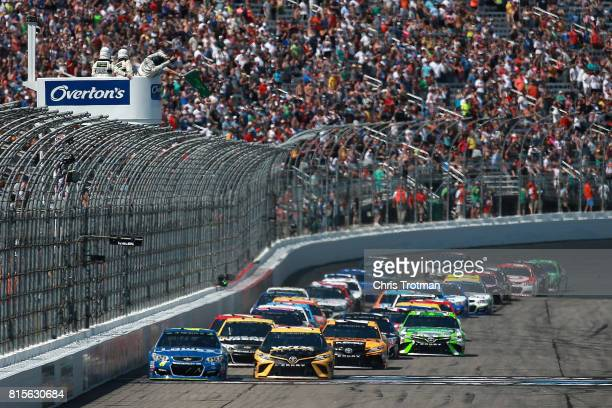 Martin Truex Jr driver of the WIX Filters Toyota and Jimmie Johnson driver of the Lowe's Chevrolet lead the field to the green flag to start the...