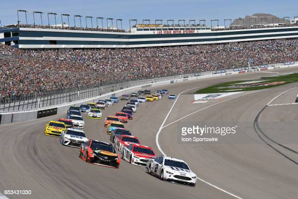 Martin Truex Jr Furniture Row Racing Toyota Camry and Brad Keselowski Team Penske Ford Fusion lead the field into turn one after a restart during the...