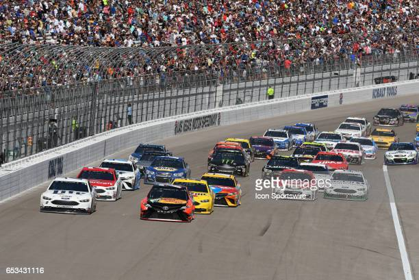 Martin Truex Jr Furniture Row Racing Toyota Camry and Brad Keselowski Team Penske Ford Fusion lead the field to turn one on a restart during the...