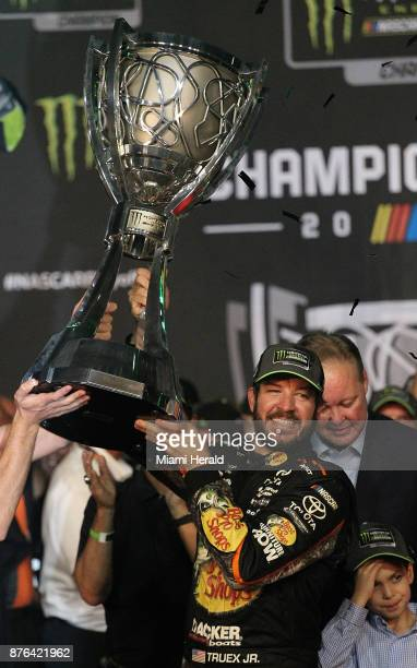 Martin Truex Jr gets help in hoisting the Monster Energy NASCAR Cup Series Championship after winning both Ford EcoBoost 400 and the series...