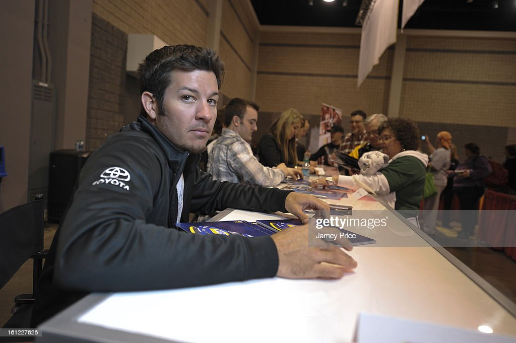 <a gi-track='captionPersonalityLinkClicked' href=/galleries/search?phrase=Martin+Truex+Jr.&family=editorial&specificpeople=184514 ng-click='$event.stopPropagation()'>Martin Truex Jr.</a> signs autographs on Saturday afternoon at the NASCAR Hall of Fame on February 9, 2013 in Charlotte, North Carolina.