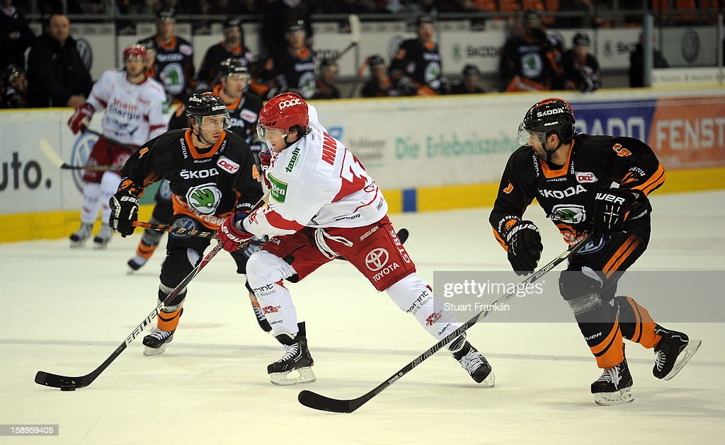 Martin Walter of Wolfsburg challenges for the puck with Christopher Minard of Cologne during the DEL match between Grizzly Adams Wolfsburg and Kolner Haie at the Volksbank BraWo Eisarena on January 4, 2013 in Wolfsburg, Germany