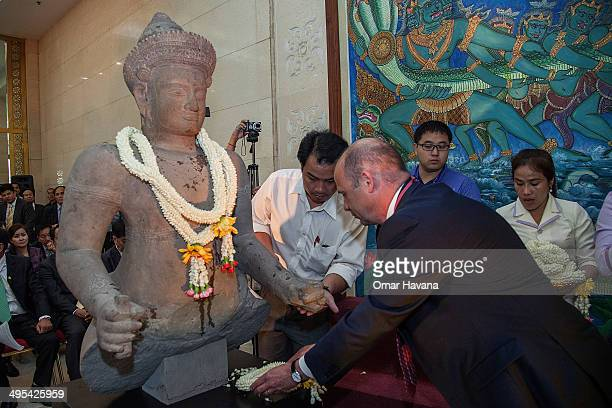Martin Wilson Global CoHead of Legal and Risks for Christie's International deposits a traditional Cambodian crown of flowers in front of the...