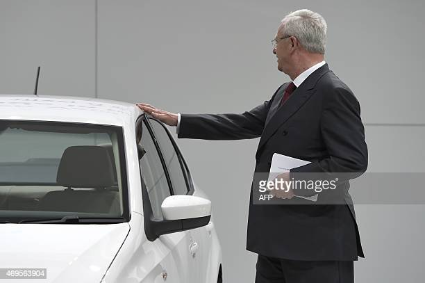 Martin Winterkorn CEO of German car maker Volkswagen stands by a Volkswagen Vento a subcompact car produced by Volkswagen India at the VW booth at...