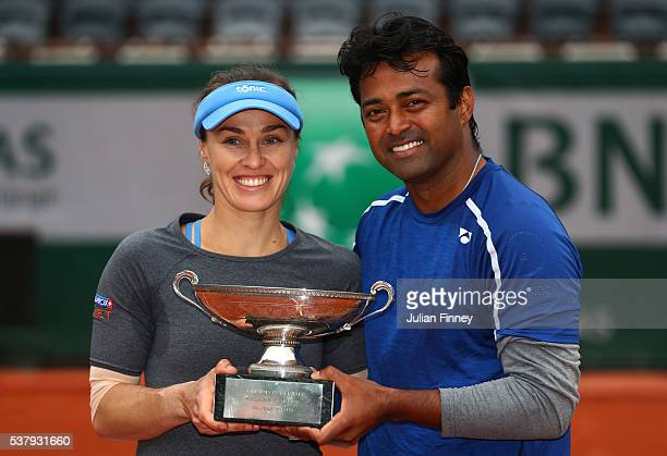 Martina Hingis of Switzerland and Leander Paes of India lift the trophy following victory during the Mixed Doubles final match against Sania Mirza of...