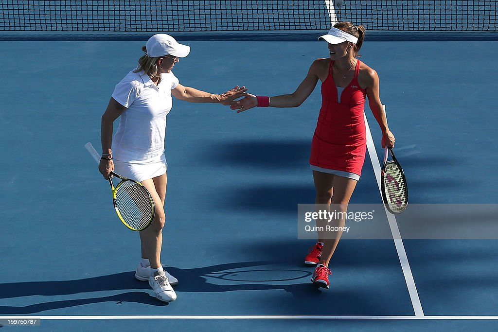 Martina Hingis of Switzerland and Martina Navratilova of the United States high five in her third round legends doubles match against Iva Majoli of Croatia and Barbara Schett of Austria during day seven of the 2013 Australian Open at Melbourne Park on January 20, 2013 in Melbourne, Australia.
