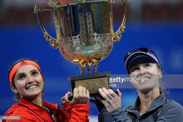 Martina Hingis of Switzerland and partner Sania Mirza of India celebrates with the trophy after winning their women's doubles final match against...