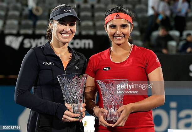 Martina Hingis of Switzerland and Sania Mirza of India celebrate and pose after winning the womens doubles final against Kristina Mladenovic and...