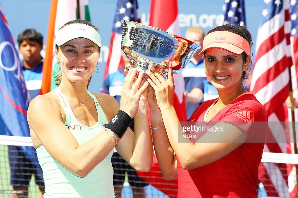 Martina Hingis of Switzerland and Sania Mirza of India celebrate with the winner's trophy after defeating Casey Dellacqua of Australia and Yaroslava...