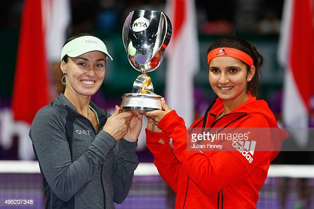 Martina Hingis of Switzerland and Sania Mirza of India hold up the Martina Navratilova Doubles Trophy after defeating Carla Suarez Navarro and...