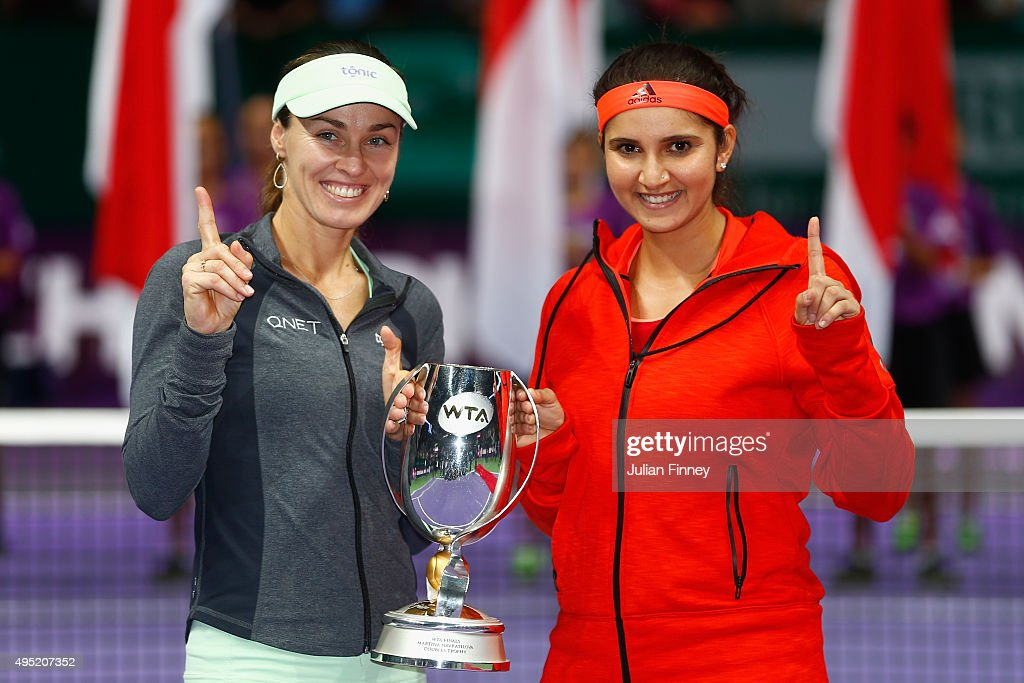 Martina Hingis of Switzerland and Sania Mirza of India hold up the Martina Navratilova Doubles Trophy after defeating Carla Suarez Navarro and Garbine Muguruza of Spain in the doubles final match during the BNP Paribas WTA Finals at Singapore Sports Hub on November 1, 2015 in Singapore.