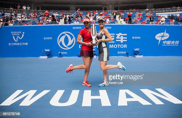 Martina Hingis of Switzerland and Sania Mirza of India pose for a picture with their trophy on day 7 of 2015 Dongfeng Motor Wuhan Open at Optics...