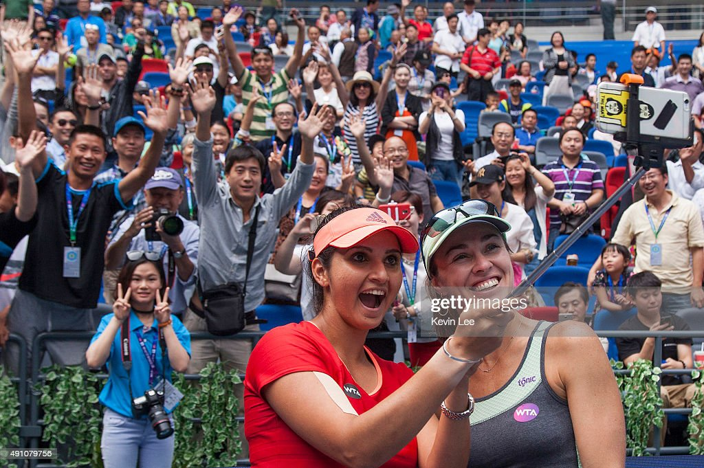 Martina Hingis of Switzerland and Sania Mirza of India take a selfie with spectators of Wuhan after winning their match on day 7 of 2015 Dongfeng Motor Wuhan Open at Optics Valley International Tennis Center on October 3, 2015 in Wuhan, China.