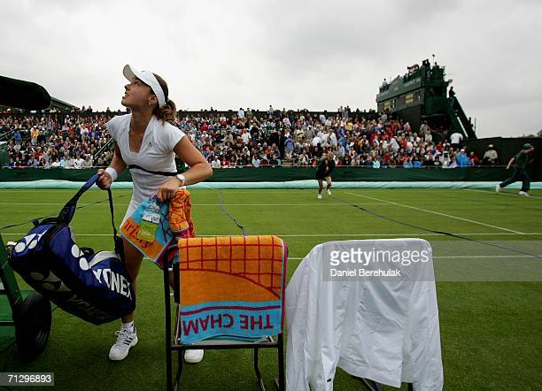 Martina Hingis of Switzerland grabs her equipment after the umpire stops play for a rain delay during her match against Olga Savchuk of Ukraine...