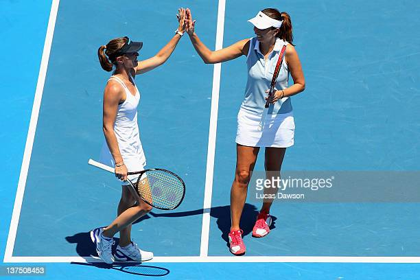 Martina Hingis of Switzerland high fives Iva Majoli of Croatia in her Legends doubles match against Nicole Bradtke of Australia and Martina...