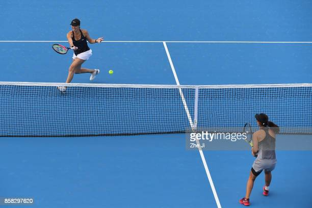Martina Hingis of Switzerland returns a shot against Gabriela Dabrowski of Canada and Yifan Xu of China during their Women's Doubles Quarterfinals...
