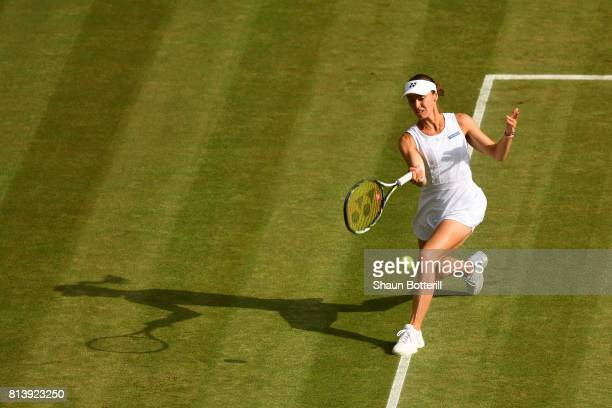 Martina Hingis of Switzerland returns partnering Jamie Murray of Great Britain during the Mixed Doubles quarter final match against Ken Skupski of...