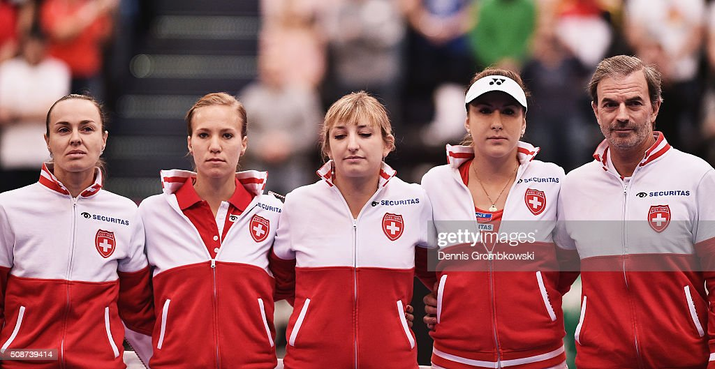 Martina Hingis, Viktorija Golubic, Timea Bacsinszky, Belinda Bencic and team captain Heinz Guenthardt of Switzerland line up for the national anthem of Switzerland during Day 1 of the 2016 Fed Cup World Group First Round match between Germany and Switzerland at Messe Leipzig on February 6, 2016 in Leipzig, Germany.