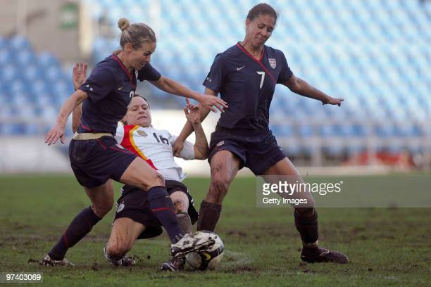 Martina Mueller of Germany Heather Mitts and Shannon Boxx of USA battle for the ball during the Women Algarve Cup match between Germany and USA on...