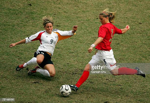 Martina Muller of Germany challenges Rachel Unitt of England for the ball during their Four Nations women's soccer match at Guangdong Olympic Stadium...