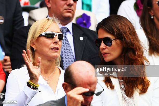 Martina Navratilova and Julia Lemigova sit in the Royal Box on Centre Court before the Ladies' Singles final match between Eugenie Bouchard of Canada...