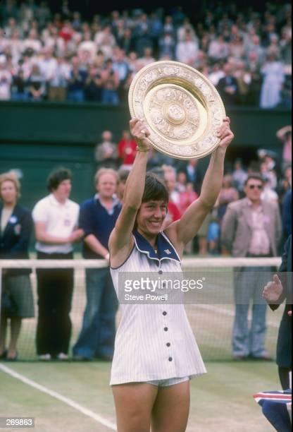 Martina Navratilova holds a trophy after winning at Wimbledon in England