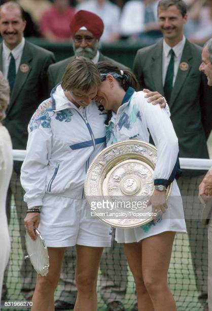 Martina Navratilova of the USA shares a moment with Conchita Martinez of Spain winner of their women's singles final each holding their tophy during...