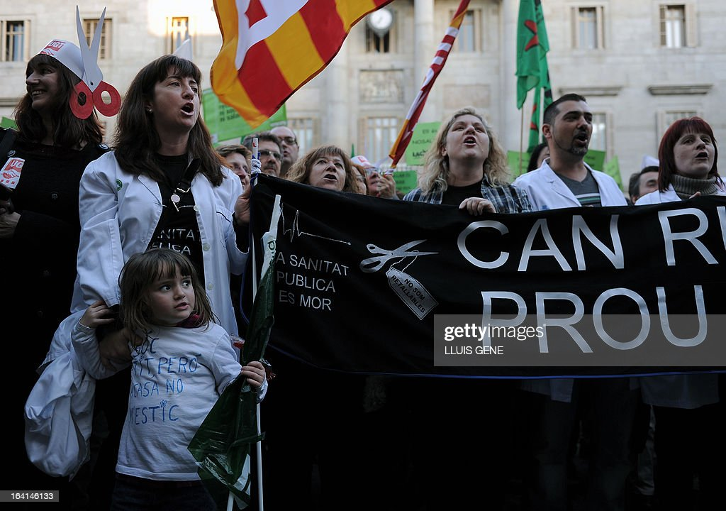 Martina, 4, wears a T-shirt reading 'I am small, but I do not stay at home' as public sector workers take part in a protest against the government's austerity measures and public spending cuts in front of the Catalan government headquarters in Barcelona on March 20, 2013.