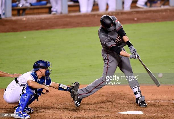 D Martinez of the Arizona Diamondbacks hits a two run homerun in front of Austin Barnes of the Los Angeles Dodgers his fourth homerun of the game to...