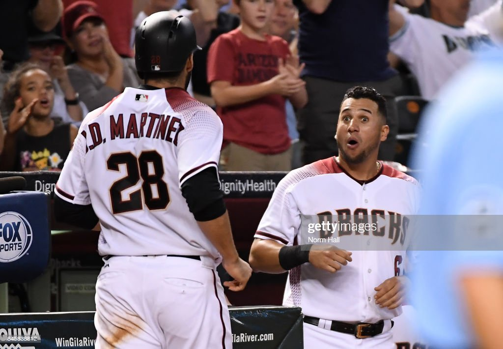 JD Martinez #28 of the Arizona Diamondbacks is congratulated by teammate David Peralta #6 after scoring against the Colorado Rockies during the fourth inning at Chase Field on September 11, 2017 in Phoenix, Arizona.