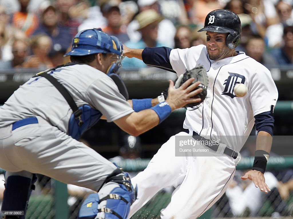 D Martinez of the Detroit Tigers beats the throw to catcher AJ Ellis of the Los Angeles Dodgers to score from second base on a single by Nick...