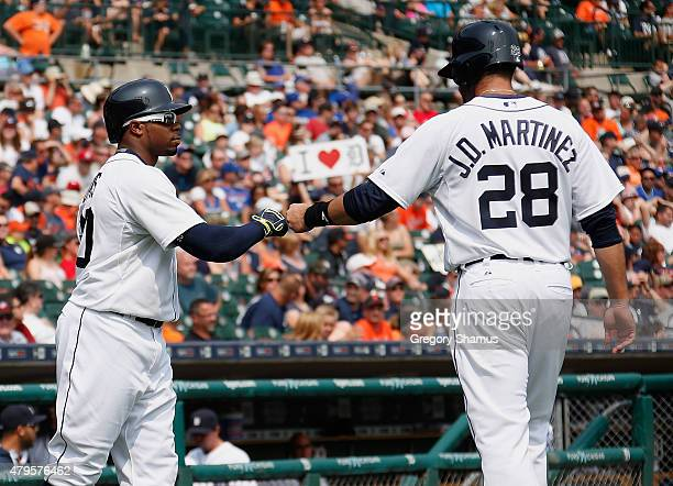D Martinez of the Detroit Tigers celebrates scoring a run in the eighth inning with Rajai Davis while playing the Toronto Blue Jays at Comerica Park...