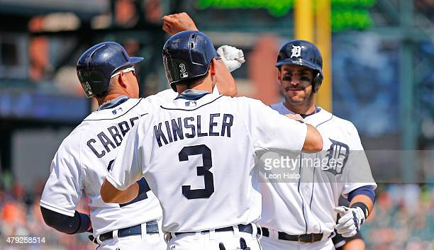 D Martinez of the Detroit Tigers celebrates with teammate Miguel Cabrera and Ian Kinsler after hitting a three run home run in the eight inning of...