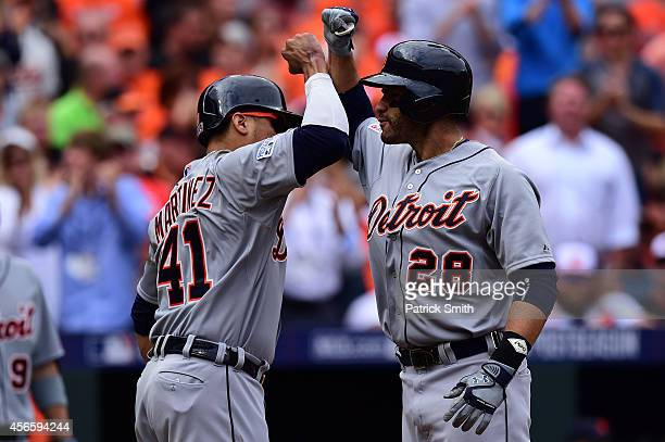D Martinez of the Detroit Tigers celebrates with teammate Victor Martinez after scoring a two run home run in the fourth inning against WeiYin Chen...