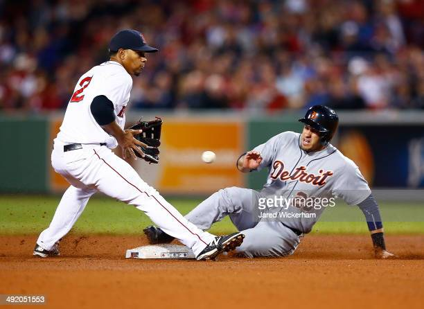 D Martinez of the Detroit Tigers slides safely into second base in front of Xander Bogaerts of the Boston Red Sox for a stolen base during the game...
