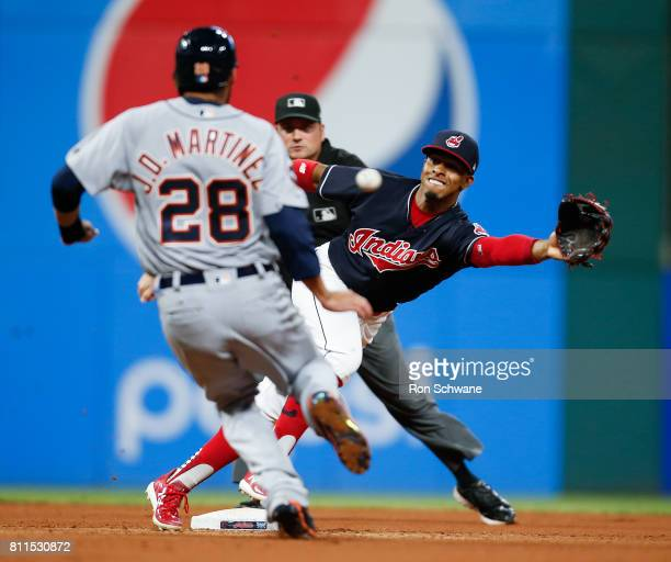 D Martinez of the Detroit Tigers steals second base as the ball gets away from Francisco Lindor of the Cleveland Indians as umpire Dan Bellino looks...