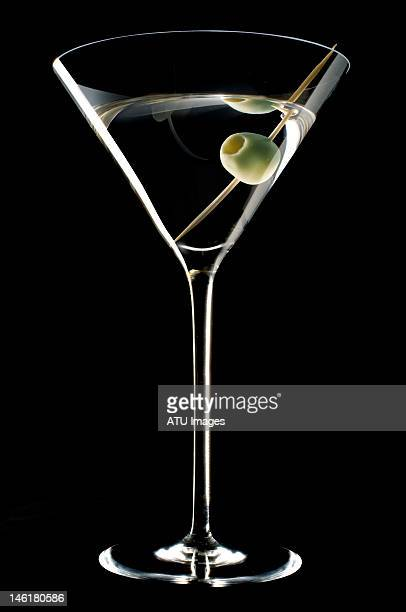 A martini and olive on a black background